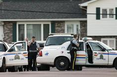 Codiac RCMP officers take cover behind their vehicle in Moncton, New Brunswick June 4, 2014.    REUTERS/Viktor Pivarov/Moncton Times & Transcript