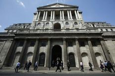 Люди проходят мимо здания Банка Англии в Лондоне 15 мая 2014 года. Банк Англии в четверг остался верен своему намерению дождаться полного восстановления экономики, не повышая ключевую ставку, несмотря на сильный рост и быстрое повышение цен на дома. REUTERS/Luke MacGregor