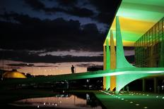 A security guard walks in front of the Planalto Palace as it is lit up in the colours of the Brazilian national flag ahead of the 2014 World Cup, in Brasilia June 5, 2014. REUTERS/Ueslei Marcelino