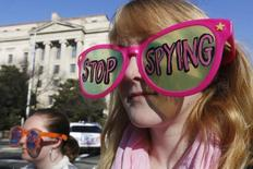 Member of the protest group, Code Pink, Cayman Macdonald protests against U.S. President Barack Obama and the NSA before his arrival at the Department of Justice in Washington, January 17, 2014. Obama banned U.S. eavesdropping on the leaders of close friends and allies on Friday and began reining in the vast collection of Americans' phone data in a series of reforms triggered by Edward Snowden's revelations.   REUTERS/Larry Downing   (UNITED STATES - Tags: POLITICS MILITARY CRIME LAW)