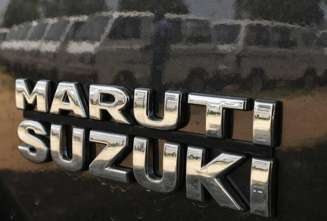 A worker is reflected on the body of a Maruti Suzuki car as he locks the door of another car at a Maruti Suzuki stockyard on the outskirts of Ahmedabad May 2, 2014. REUTERS/Amit Dave/Files