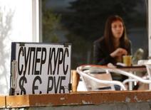 Женщина в кафе на фоне вывески обменного пункта в Севастополе 24 марта 2014 года. Рубль завершает волатильную неделю в плюсе после неплохой трудовой статистики США и на фоне надежд на деэскалацию украинского конфликта. REUTERS/Vasily Fedosenko