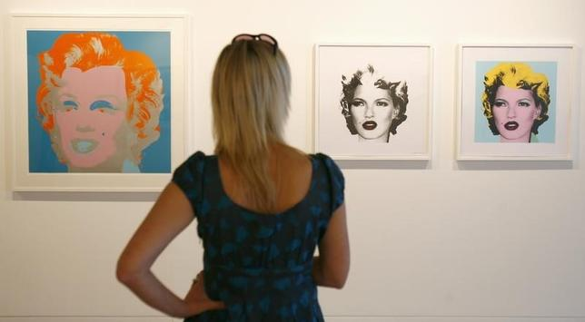An woman looks at ''Marilyn 29'' (L) by artist Andy Warhol and ''Kate Moss (Black)'' and ''Kate Moss (Yellow)'' by Banksy, part of the exhibition Warhol vs Banksy at The Hospital in Covent Garden, London, August 9, 2007.  REUTERS/Luke MacGregor