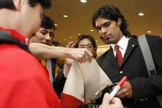SC Internacional's Fernandao of Brazil signs an autograph for fans on his arrival for the FIFA Club World Cup at Narita International Airport near Tokyo December 7, 2006. REUTERS/Kiyoshi Ota