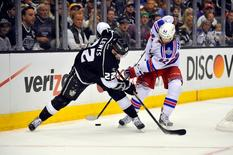 Jun 7, 2014; Los Angeles, CA, USA; Los Angeles Kings center Trevor Lewis (22) battles for the puck with New York Rangers left wing Carl Hagelin (62) in the third period during game two of the 2014 Stanley Cup Final at Staples Center. Mandatory Credit: Gary A. Vasquez-USA TODAY Sports