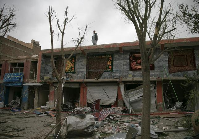 A man stands on the roof top of shops damaged in bomb blasts in Kabul June 6, 2014.  REUTERS/Ahmad Masood