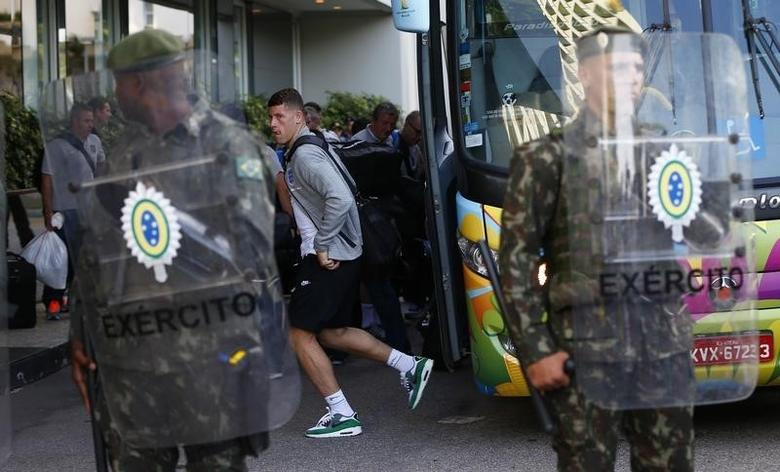 England national soccer player Ross Barkley (C) walks past Brazilian army personal as he arrives at the team hotel in Rio de Janeiro June 8, 2014. The 2014 World Cup in Brazil begins on June 12.  REUTERS/Eddie Keogh