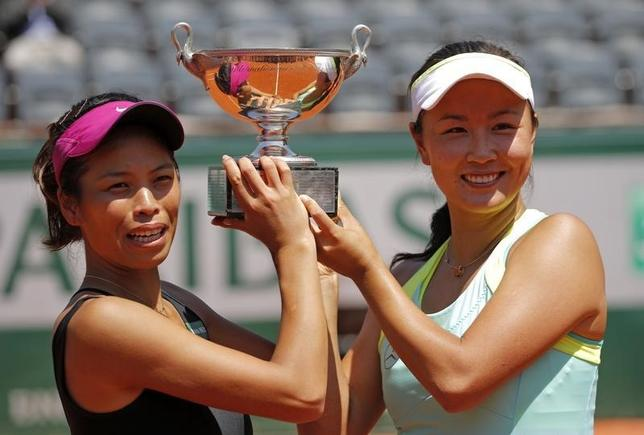 Peng Shuai of China (R) and Hsieh Su-Wei of Taiwan pose with the trophy during the ceremony after winning their women's doubles final match against Sara Errani and Roberta Vinci of Italy at the French Open Tennis tournament at the Roland Garros stadium in Paris June 8, 2014. REUTERS/Stephane Mahe