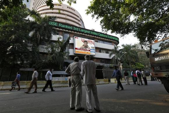 People watch a large screen displaying benchmark share index on the facade of the Bombay Stock Exchange (BSE) building in Mumbai December 9, 2013. REUTERS/Mansi Thapliyal/Files