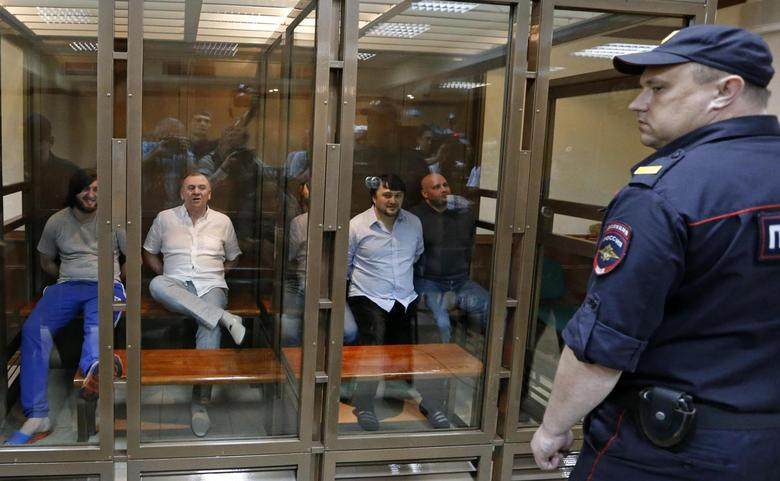 Defendants in the murder trial of Russian journalist and human rights activist Anna Politkovskaya, (L-R) Ibragim Makhmoudov, Lom-Ali Gaitukayev, Dzhabrail Makhmoudov, Rustam Makhmoudov and Sergei Khadzhikurbanov sit inside a glass-walled cage, while a policeman stands guard in the foreground, during a court hearing in Moscow, June 9, 2014. REUTERS/Sergei Karpukhin