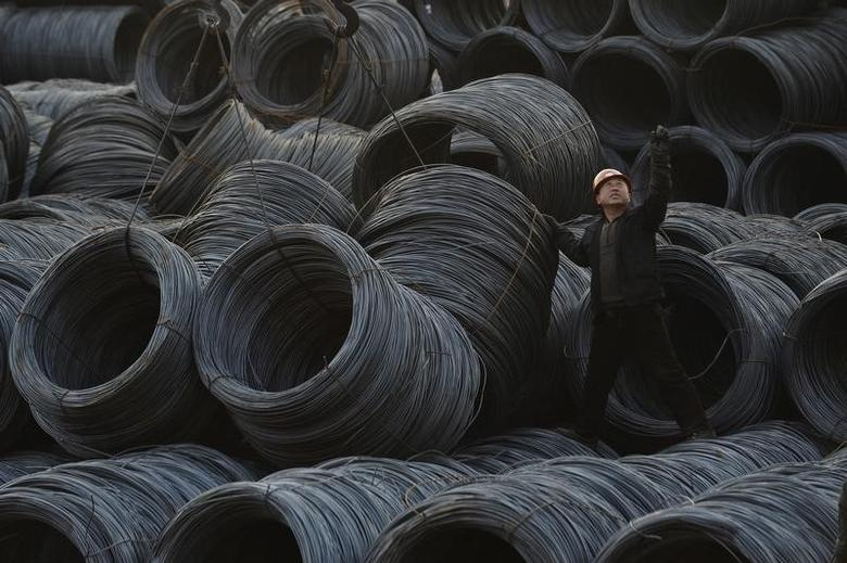 A labourer works on piles of steel coils in Taiyuan, Shanxi province, February 22, 2013. REUTERS/Jon Woo/Files