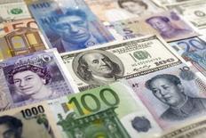Imagen tomada en Varsovia de varias monedas del mundo incluyendo el yuan chino, el yen japonés, el dólar estadounidense, el euro, la libra esterlina, el franco suizo. 26 de enero del 2011. El peso mexicano continuaría esta semana afectado por el inesperado recorte de tasas de interés que dispuso el viernes el Banco de México, organismo monetario del país, a contracorriente de otras monedas de la región, que todavía disfrutan del buen clima financiero externo. REUTERS/Kacper Pempel