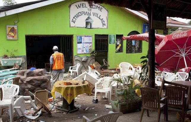 An investigator walks through the remains of an Ethiopian-themed restaurant that was hit by an explosion in Kampala, July 12, 2010.  REUTERS/Benedicte Desrus