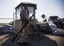 Пророссийский сепаратист на оставленном украинскими пограничниками пункте пропуска на российской границе в Червонопартизанске 7 июня 2014 года. REUTERS/Shamil Zhumatov