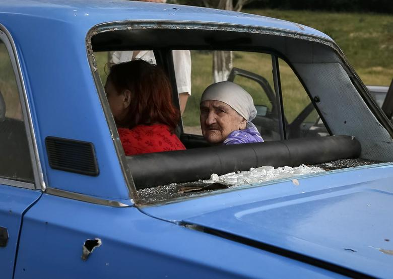 An old woman looks from inside a car with bullet holes and shattered windows as she flees fighting in the eastern Ukrainian town of Slaviansk June 9, 2014. REUTERS/Gleb Garanich
