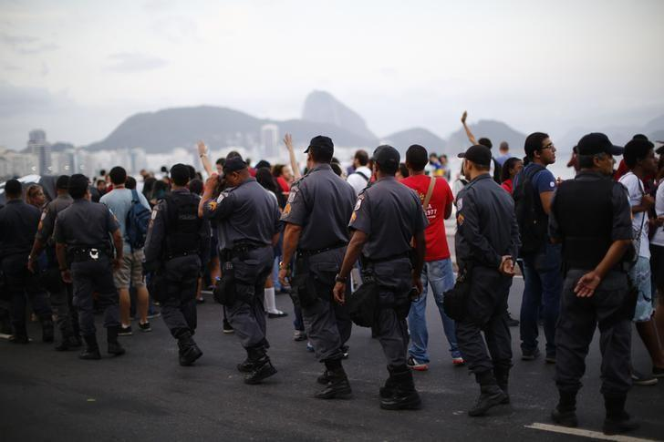 Police stand guard as anti-FIFA World Cup demonstrators take part in a march at Copacabana beach in Rio de Janeiro June 9, 2014.  REUTERS/Jorge Silva