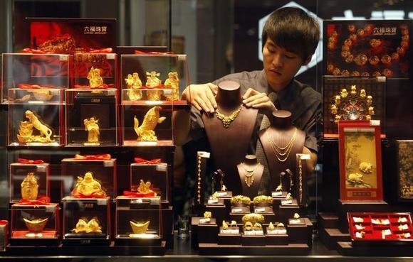 An employee adjusts a gold necklace on a displaying model near glass cases containing gold figurines at a gold shop in Wuhan, Hubei province August 25, 2011. REUTERS/Stringer/Files