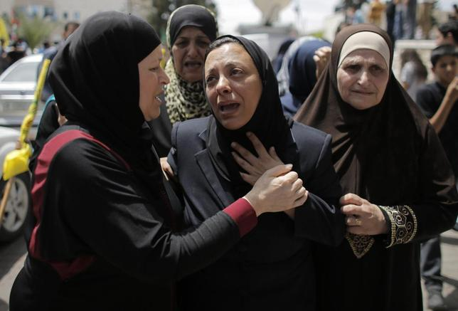 The mother (C) of Palestinian man Nadim Nuwara, who was shot dead by Israeli forces on Thursday, mourns during his funeral in the West Bank city of Ramallah May 16, 2014.    REUTERS/Ammar Awad