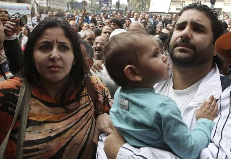 Alaa Abdel Fattah (R), one of the activists who was summoned by the public prosecutor on whether he had a role in the recent violent anti-Islamists protests, arrives with his wife and child to the public prosecutor's office in Cairo, in this file March 26, 2013 photo. REUTERS/Asmaa Waguih