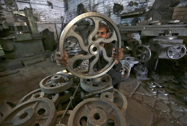A worker checks the dimension of a wheel used in textile machinery inside a factory in the western Indian city of Ahmedabad March 12, 2014. India's industrial production grew for the first time in four months in January, posting annual growth of 0.1 percent, government data showed on Wednesday. REUTERS/Amit Dave (INDIA - Tags: BUSINESS EMPLOYMENT) - RTR3GR9Q