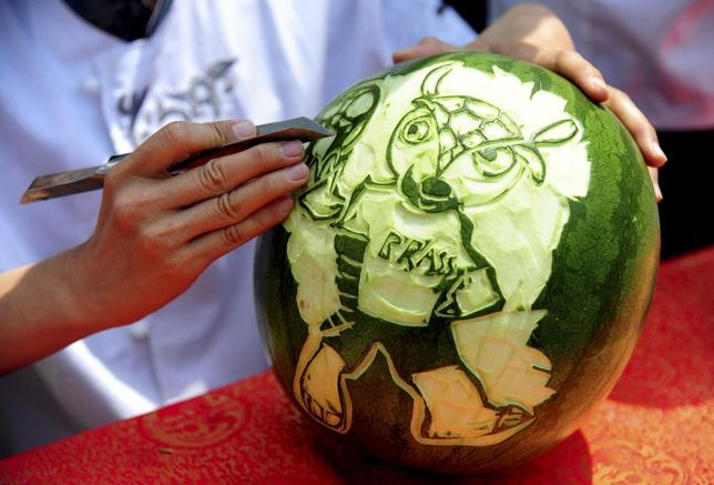 A student carves the 2014 World Cup mascot, Fuleco the Armadillo, on a watermelon ahead of the 2014 World Cup in Brazil, in Shenyang, Liaoning province, June 10, 2014. REUTERS/China Daily