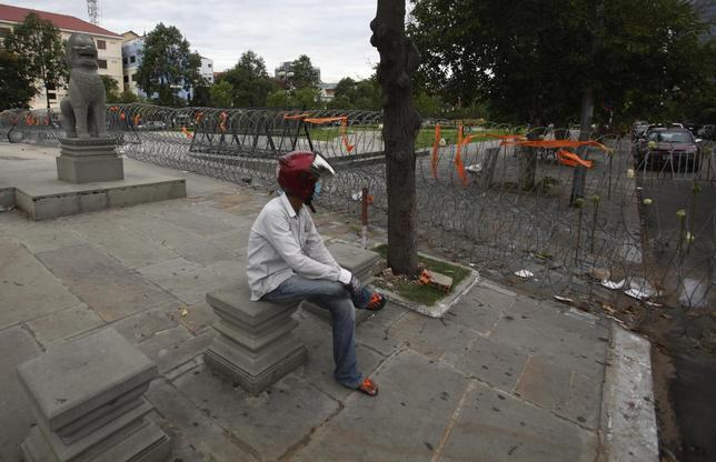 A man sits near Freedom Park which is blocked off by a barbed wire fence set up by police officers in central Phnom Penh June 11, 2014.  REUTERS/Samrang Pring