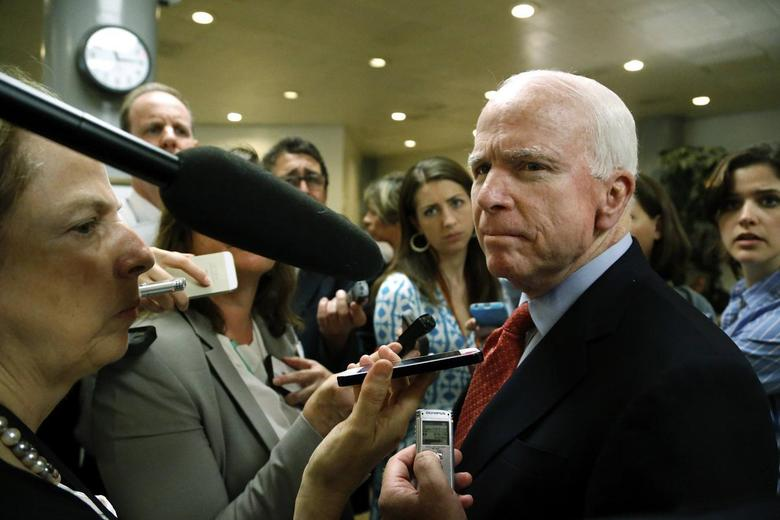 U.S. Senator John McCain (R-AZ) (R) talks to reporters after a closed-door Senate Armed Services Committee briefing on the Bergdahl prisoner swap at the U.S. Capitol in Washington June 10, 2014. REUTERS/Jonathan Ernst