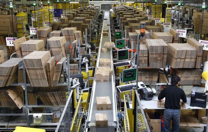 Workers pack boxes at Amazon's logistics centre in Graben near Augsburg December 16, 2013. REUTERS/Michaela Rehle