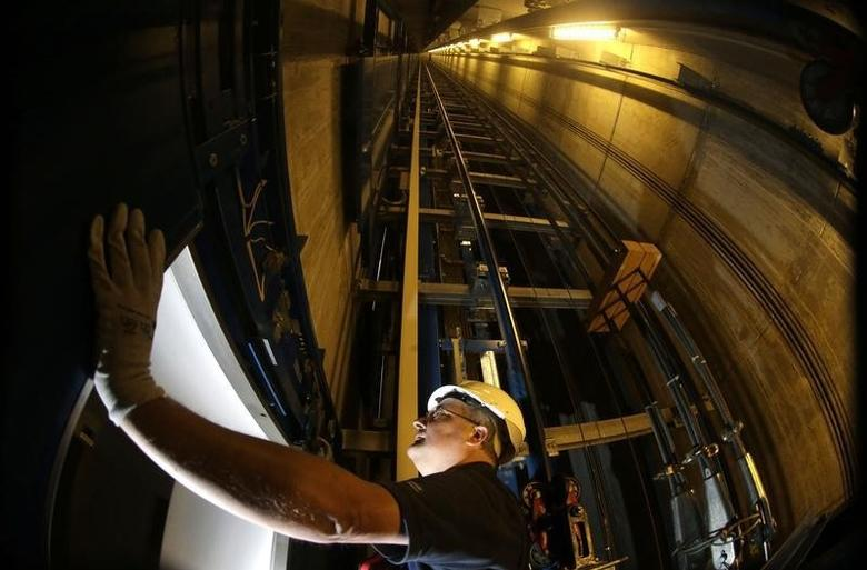 A service engineer of Germany's industrial conglomerate ThyssenKrupp AG inspects the door inside an elevator shaft at an office building in Berlin.The elevators business will be one of the German firm's pillars after its biggest corporate revamp in almost 15 years, along with other high-tech, high-margin businesses such as plant technology, automotive components and submarines. Picture taken September 17, 2013. REUTERS/Tobias Schwarz