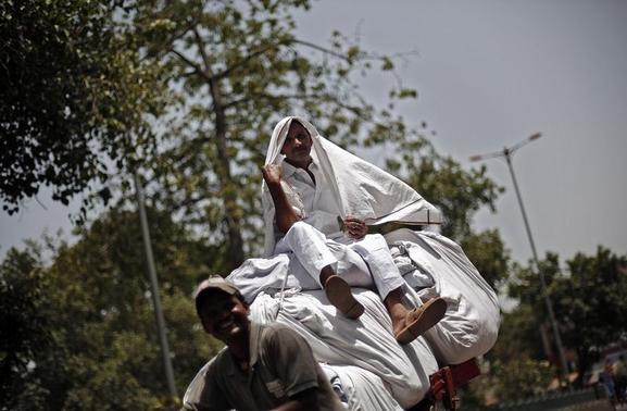 A man protects himself from sun with a cloth as he sits on top of a cycle rickshaw carrying laundry on a hot summer day in the old quarters of Delhi June 11, 2014. REUTERS/Adnan Abidi