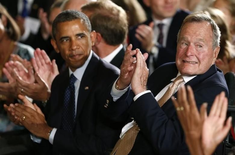 U.S. President Barack Obama and former President George H. W. Bush (R) applaud during an event to honor the winner of the 5,000th Daily Point of Light Award at the White House in Washington July 15, 2013.   REUTERS/Kevin Lamarque