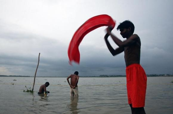 A Hindu devotee dries his clothes after taking a holy dip in Sangam, the confluence of the three holy rivers Ganga, Yamuna and Saraswati during the Hindu month of Shravan, in  Allahabad July 17, 2011. REUTERS/Jitendra Prakash/Files