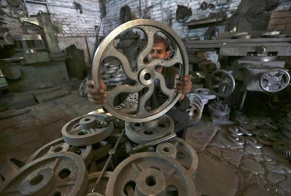 A worker checks the dimension of a wheel used in textile machinery inside a factory in Ahmedabad March 12, 2014. REUTERS/Amit Dave/Files