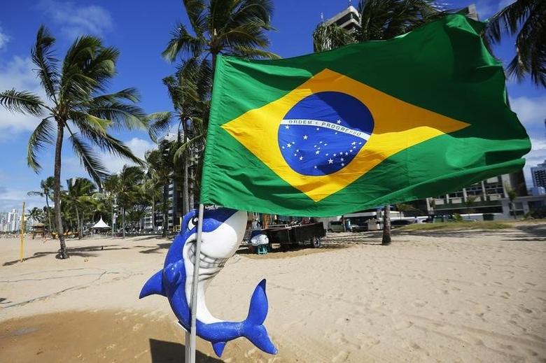 A toy shark appears to hold a Brazilian flag, on the beach where signs warn swimmers of the risk of shark attack, in Recife June 12, 2014.   REUTERS/Brian Snyder