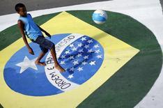 Un niño domina una pelota sobre una bandera brasileña pintada en una calle en Mangaratiba, jun 12 2014   REUTERS/Alessandro Garofalo