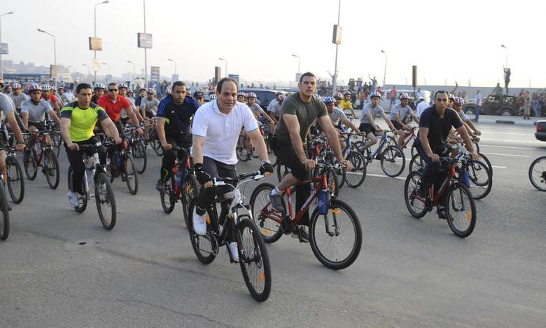 Egypt's President Abdel Fattah al-Sisi (front, white) rides a bicycle with few hundred Egyptians outside the military college in Cairo, June 13, 2014, in this handout picture provided by the Egyptian Presidency.  REUTERS/Egyptian Presidency/Handout via Reuters