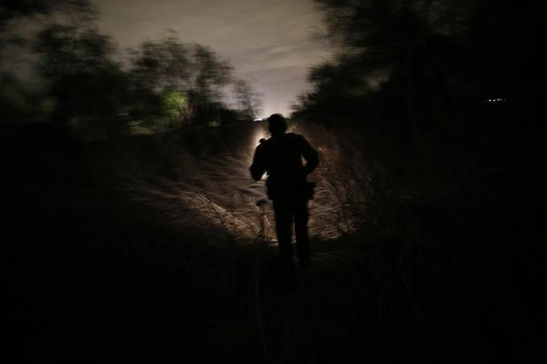 A U.S. Border Patrol agent from the Rio Grande Valley Sector searches for a group of illegal immigrants who crossed the Rio Grande River in Mission, Texas March 28, 2013.  REUTERS/Eric Thayer