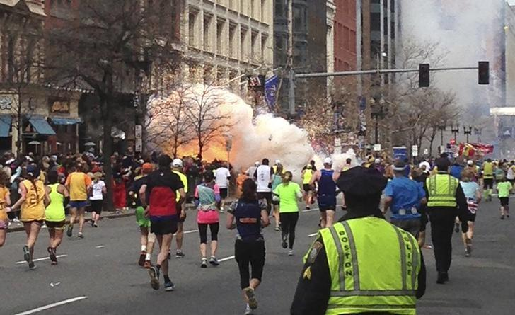 Runners continue to run towards the finish line of the Boston Marathon as an explosion erupts near the finish line of the race in this photo exclusively licensed to Reuters by photographer Dan Lampariello after he took the photo in Boston, Massachusetts, April 15, 2013.   REUTERS EXCLUSIVEMandatory Credit REUTERS/Dan Lampariello