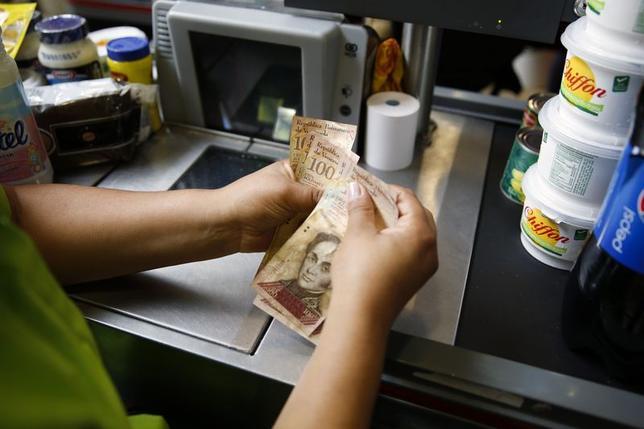 A cashier counts Venezuelan bolivar bills at a supermarket checkout line in Caracas June 13, 2014. REUTERS/Carlos Garcia Rawlins