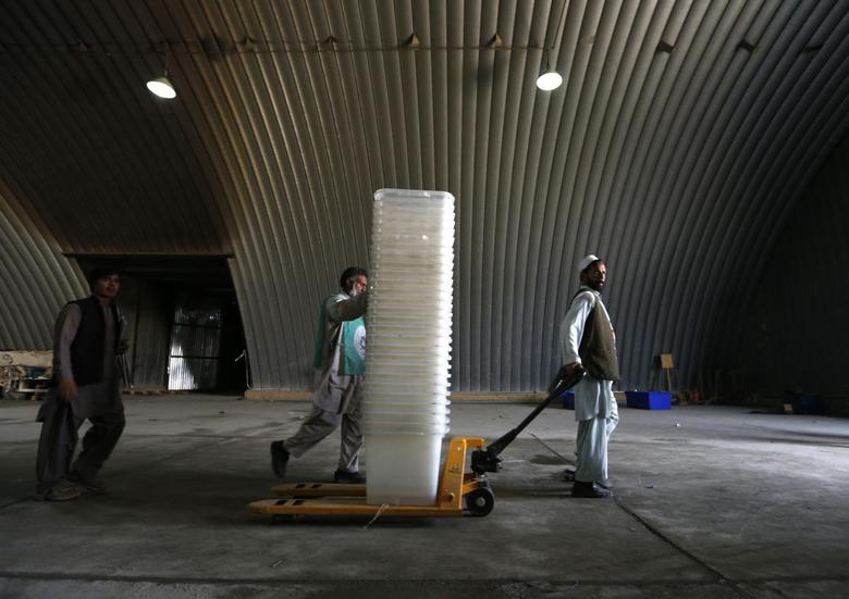 Afghan election commission workers move ballot boxes and election material in a warehouse in Kabul June 13, 2014.  REUTERS/Mohammad Ismail