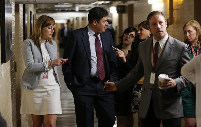 U.S. Representative Raul Labrador (R-ID) (2ndL) talks to reporters gathered to ask members about House Majority Leader Eric Cantor's Republican primary election defeat in a hallway of the U.S. Capitol in Washington on June 11, 2014. REUTERS/Jim Bourg