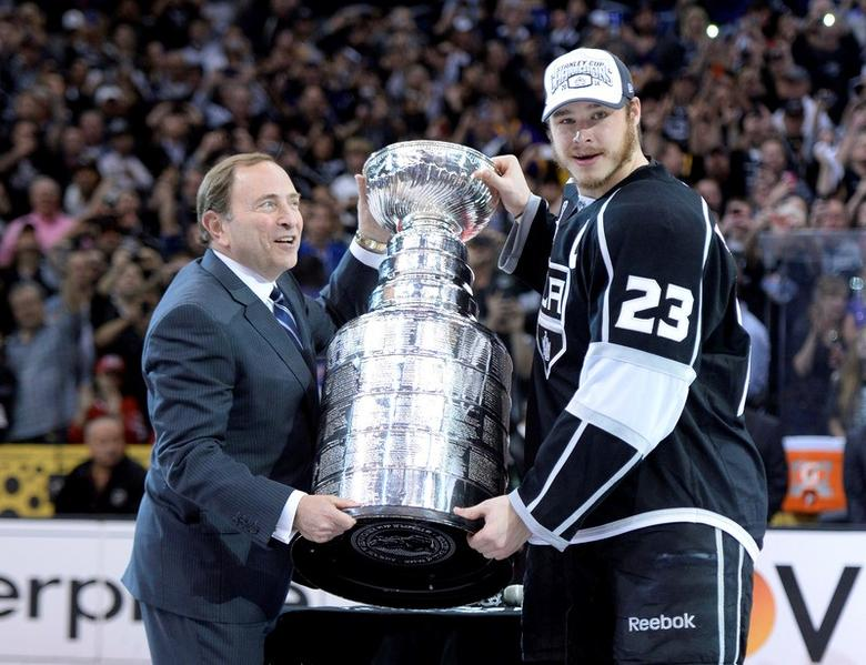 Jun 13, 2014; Los Angeles, CA, USA; NHL commissioner Gary Bettman (left) presents Los Angeles Kings right wing Dustin Brown (23) with the Stanley Cup after defeating the New York Rangers game five of the 2014 Stanley Cup Final at Staples Center. Mandatory Credit: Gary A. Vasquez-USA TODAY Sports