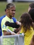 Neymar, que mudou o corte de cabelo, dá autógrafos durante treino na Granja Comary, em Teresópolis. 15/6/2014.  REUTERS/Marcelo Regua