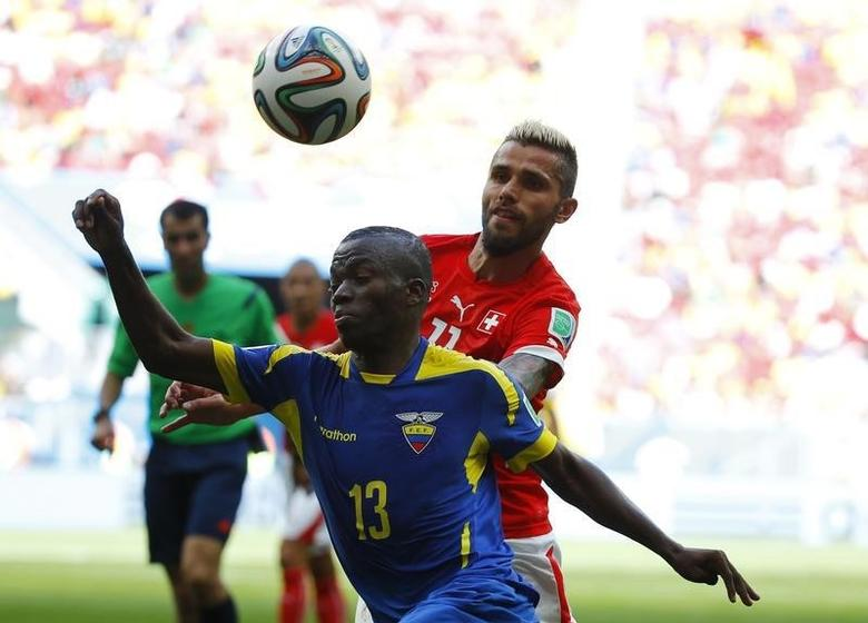 Ecuador's Enner Valencia (front) fights for the ball with Switzerland's Valon Behrami during their 2014 World Cup Group E soccer match at the Brasilia national stadium in Brasilia, June 15, 2014.  REUTERS/Paul Hanna