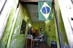 A barber shaves a customer while the World Cup soccer match between Colombia and Greece is shown on a television (top) at the port market in Cuiaba June 14, 2014.      REUTERS/Eric Gaillard