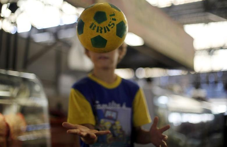 Ricardo Pineto, 8 years old, plays with his ball after filling a bottle with water for his family in the port market in the World Cup venue of Cuiaba June 14, 2014. REUTERS/Amr Abdallah Dalsh