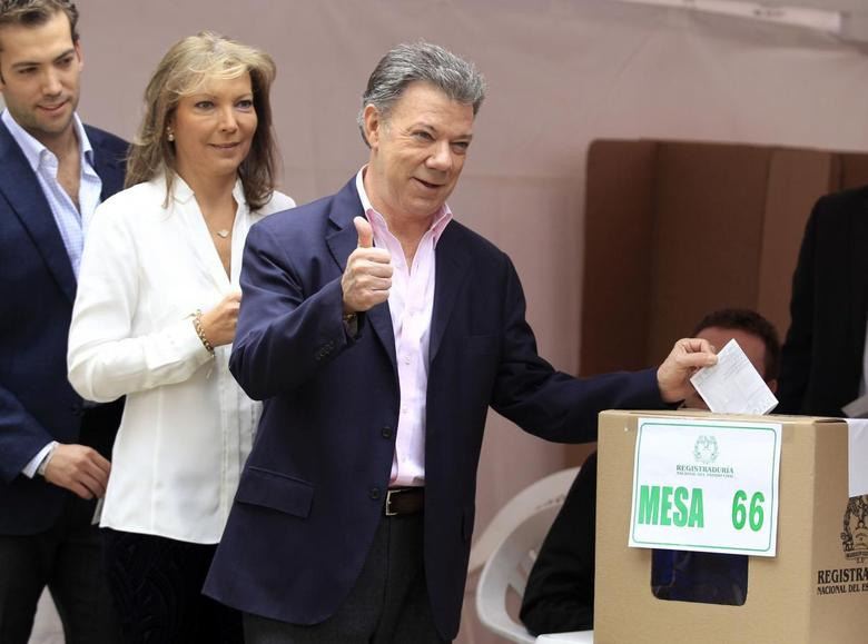 President Juan Manuel Santos gestures before casting his vote as he is accompanied by his wife Maria Clemencia and son Martin in Bogota June 15, 2014.  REUTERS/Jaime Saldarriaga