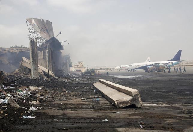 Planes are seen near a section of a damaged building (L) at Jinnah International Airport, after Sunday's attack by Taliban militants, in Karachi June 10, 2014. REUTERS/Athar Hussain