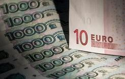 Купюры валют рубль и евро в Москве 17 февраля 2014 года. Рубль дешевеет утром понедельника на фоне бегства от риска из-за геополитических рисков, а также отсутствия договоренностей по газу между Украиной и Россией. REUTERS/Maxim Shemetov