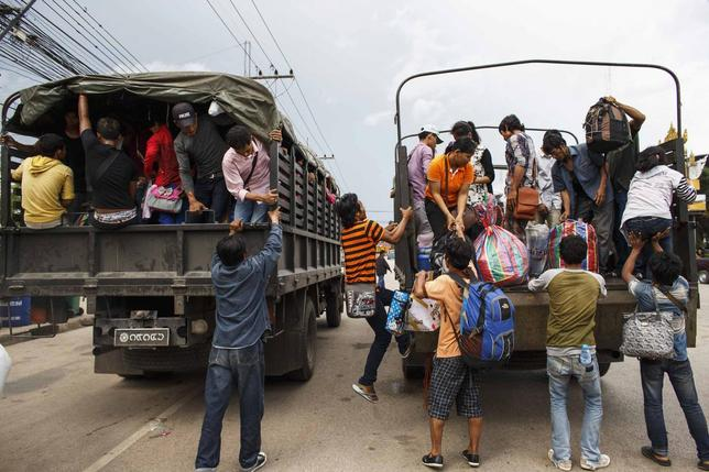 Cambodian workers ride on military trucks as they prepare to cross the Thai-Cambodia border at Aranyaprathet in Sa Kaew June 15, 2014. REUTERS/Athit Perawongmetha